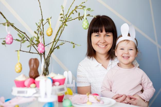 Concetto di famiglia, felicità e vacanze primaverili - ritratto di madre felice con piccola figlia carina e tavolo decorato con cupcakes alla crema e uova di pasqua dipinte colorate