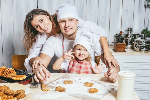 Famiglia, figlia felice con papà e mamma nella cucina di casa ridendo e preparando il cibo insieme, con amore