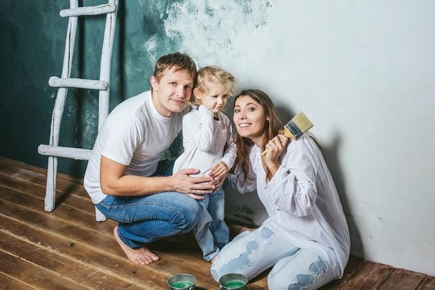 Famiglia, figlia felice con mamma e papà che fanno riparazioni a casa, dipingono i muri, insieme con amore