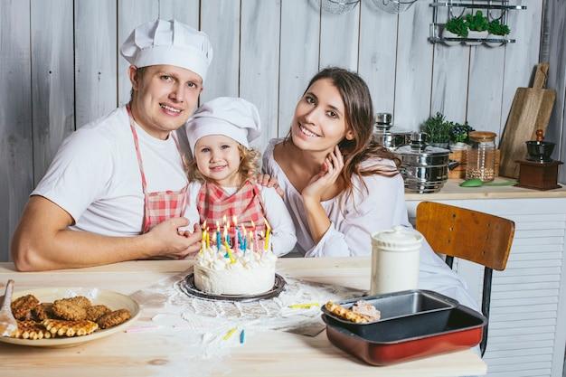 Famiglia, figlia felice con mamma e papà a casa in cucina ridono e accendono le candeline sulla torta di compleanno