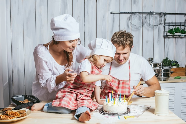 Famiglia, figlia felice con mamma e papà a casa in cucina a ridere e cuocere una torta di compleanno insieme, con amore