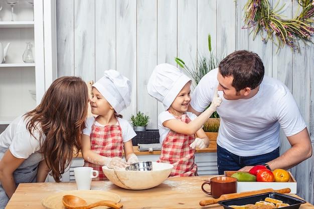 Famiglia felice mamma, papà e due sorelle gemelle ragazze in cucina cuociono i biscotti dalla farina.