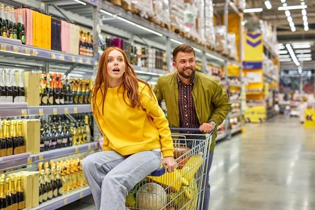 La famiglia si diverte nel corridoio del negozio di alimentari, la donna si siede sul carrello e si diverte a fare shopping con il marito. donna sorpresa ha visto qualcosa di interessante