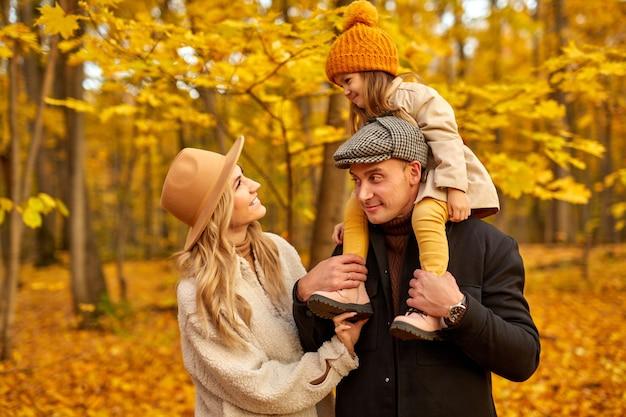La famiglia si diverte in autunno parco natura, coppia caucasica e abbracciare il bambino