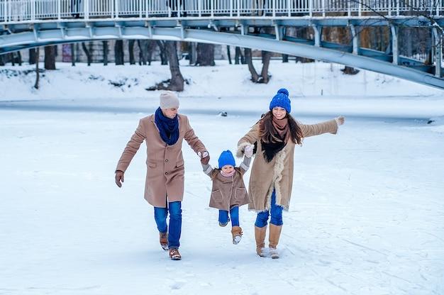 La famiglia si diverte su un lago ghiacciato nel parco sullo sfondo del ponte
