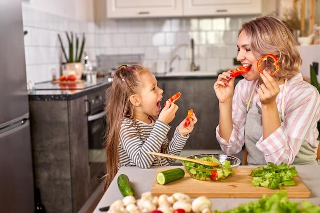 La famiglia si diverte mentre cucina in cucina, adorabile donna con bambina che intaglia verdure fresche, sorridi, goditi il processo