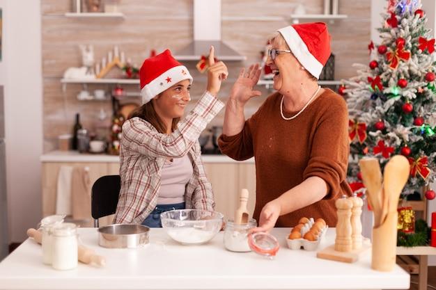 La famiglia si diverte insieme a giocare con la farina mentre cucina il dessert di pan di zenzero