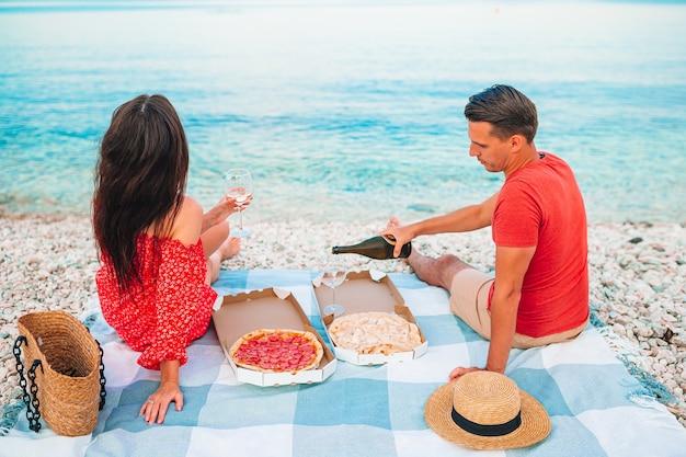 Famiglia che ha un picnic sulla spiaggia