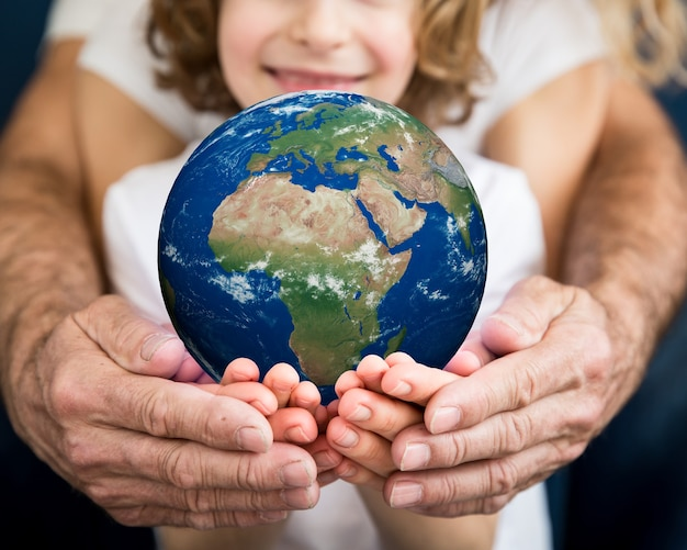 Famiglia che tiene il pianeta 3d nelle mani. concetto di vacanza per la giornata della terra. elementi di questa immagine fornita dalla nasa