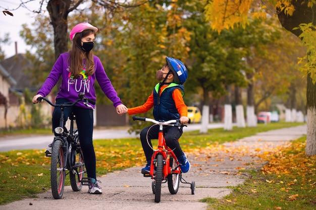 Vacanza in famiglia. fratello e sorella in autunno parco divertendosi in sella a biciclette in papaveri hashite. pandemia e concetto di virus.