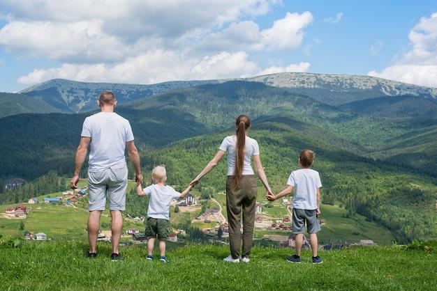 Vacanza in famiglia. i genitori ei due figli ammirano la vista sulla vallata. montagne in lontananza. vista posteriore