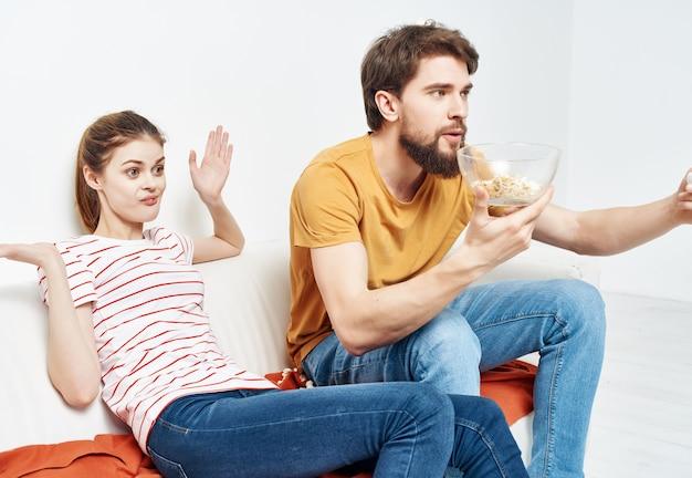 Famiglia a casa seduta sul divano con popcorn a guardare film divertenti