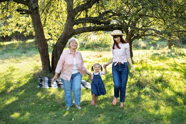 Momenti congiunti familiari, felice relazione tra generazioni diverse. ritratto di famiglia multigenerazionale femminile, che cammina fuori nel giardino soleggiato estivo e si diverte.
