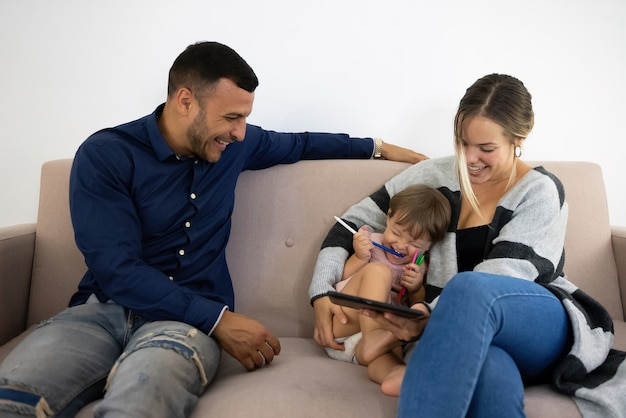 Famiglia che ride e si diverte sul divano con il tablet