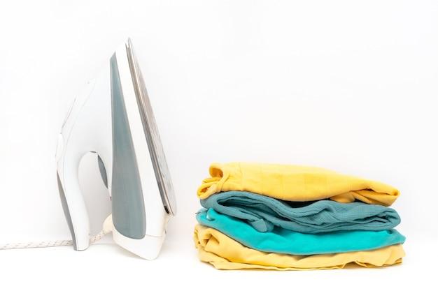 Mucchio della lavanderia della famiglia di vestiti variopinti isolati con il ferro. pila di vestiti di colore alla moda da vicino.