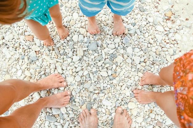 Gambe della famiglia nella sabbia del mare