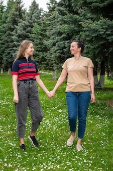 Famiglia e concetto di svago. madre e figlia sorridenti felici che tengono le mani e che camminano nel parco