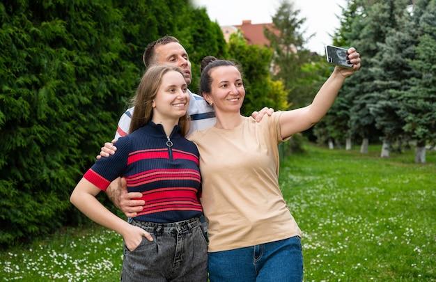 Famiglia, tempo libero e concetto di tecnologia. madre felice, padre e figlia che prendono la foto del selfie dallo smartphone nel parco