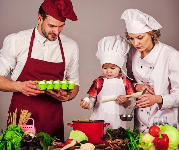 Stile di vita familiare. padre madre e figlio che cucinano insieme in cucina. cibo sano a casa.