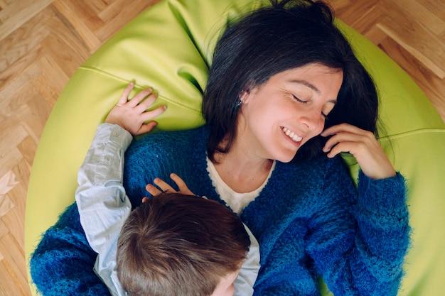 Stile di vita familiare all'interno della casa con i bambini. animazione per bambini piccoli al chiuso. sorella amorevole che abbraccia fratello essendo giocoso. concetto di infanzia. madre single che gioca con suo figlio a casa.