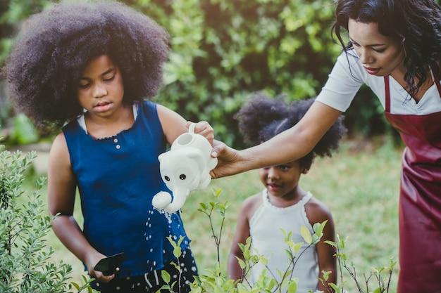 Attività di giardinaggio adorabile della famiglia che innaffia le piante verdi con i bambini durante il soggiorno a casa per ridurre lo scoppio del coronavirus. bambini che innaffiano la pianta in cortile.