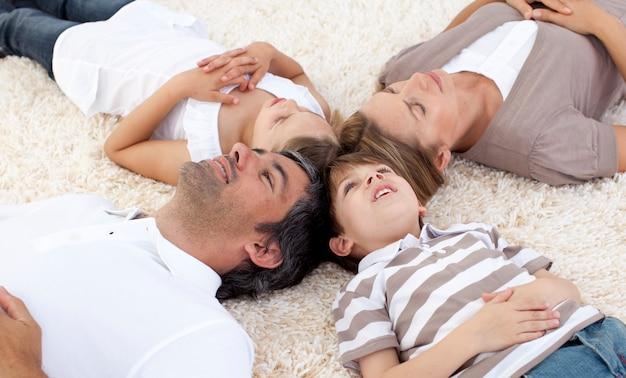 Famiglia sdraiato sul pavimento a casa con le teste insieme