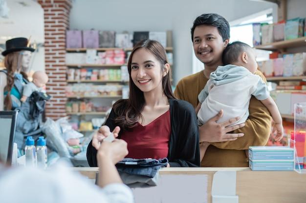 Famiglia che effettua un pagamento al baby shop utilizzando la carta di credito alla cassa