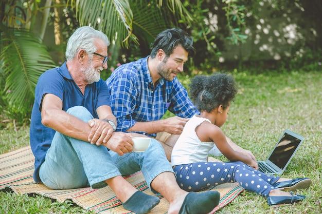 Uomo di famiglia con picnic più anziano che sembra felice gioco di cura dei bambini con la figlia al parco del cortile all'aperto.