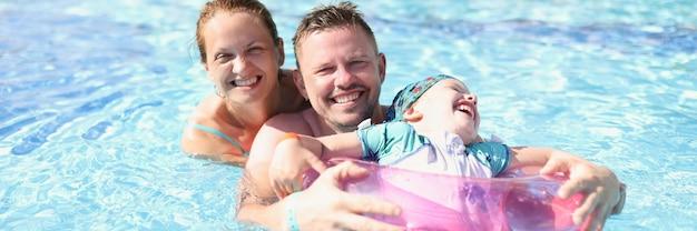 Famiglia mamma papà e figlia ridono e nuotano in piscina