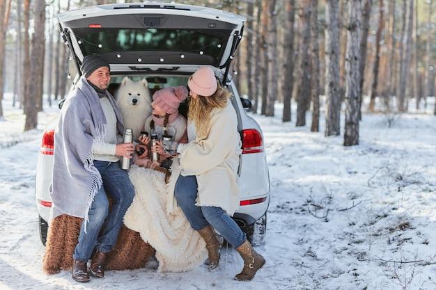 Famiglia di mamma, papà e figlia in giacche calde e un divertente cane samoiedo bianco