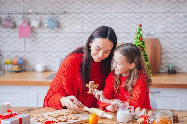 La famiglia di mamma e figlia prepara i biscotti di natale in cucina