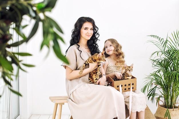 Madre e figlia di famiglia belle e felici con i piccoli gattini del bengala insieme