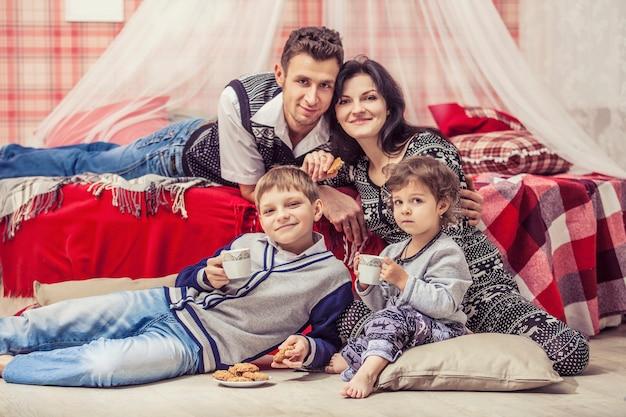 Famiglia madre padre bambini in camera da letto a casa nell'interno rosso di natale