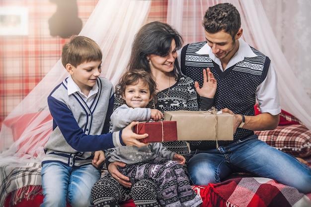Madre di famiglia, padre e figli si scambiano regali nell'arredamento invernale della tua casa