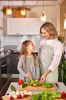 Madre di famiglia con figlia che cucinano insieme, ragazza felice è felice di aiutare la madre a preparare l'insalata, mescolando verdure fresche