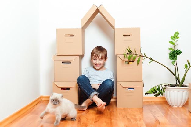 La famiglia si trasferisce in un nuovo appartamento. giornata in movimento. bambino felice e gatto che si divertono insieme al giorno del trasloco nella nuova casa.