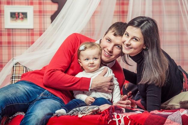Famiglia mamma papà e bambino insieme a casa nell'atmosfera accogliente delle camere da letto in interni invernali