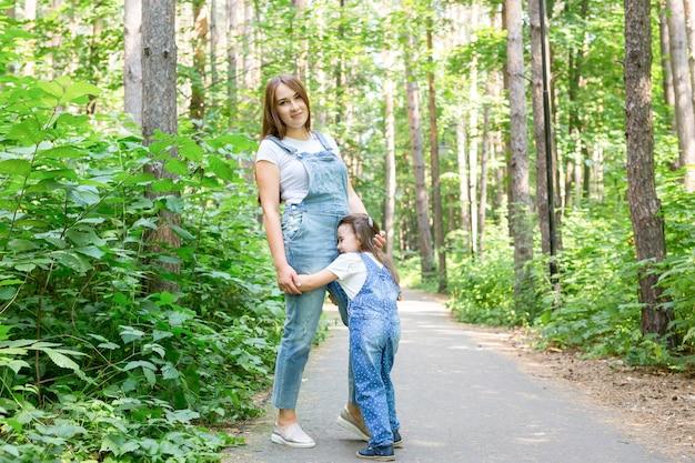 Famiglia, natura, concetto di persone - figlia che abbraccia sua madre nel parco.