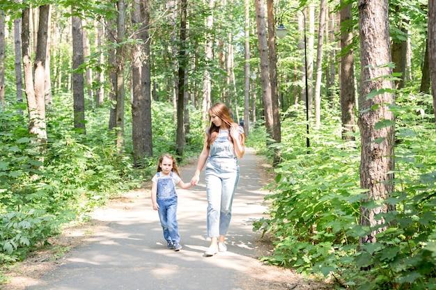 Concetto di famiglia, natura e persone - mamma e figlia trascorrono del tempo insieme in una passeggiata nel verde del parco