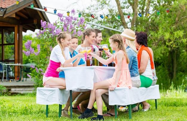 Famiglia e vicini di casa alla festa in giardino a bere, seduti davanti a una casa con amici e familiari