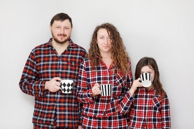 Famiglia in pigiama su uno sfondo bianco. papà, mamma e figlia piccola con tazze di tè.
