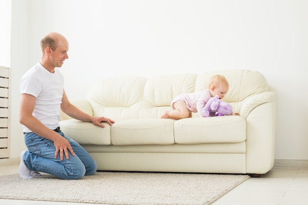 Concetto di famiglia, genitorialità e paternità - padre felice che gioca con la piccola bambina a casa