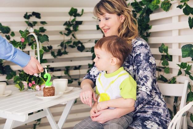 Famiglia, genitorialità, buon compleanno e concetto di vacanza - genitori e figli felici a un tavolo che bevono tè e mangiano torta.