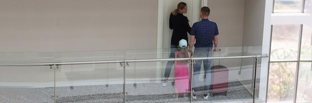 Famiglia genitori e bambino aprono la camera in hotel al momento del check-in