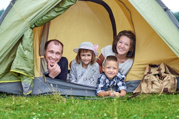 Famiglia genitori e due bambini nella tenda da campo. felice madre, padre, figlio e figlia in vacanza estiva