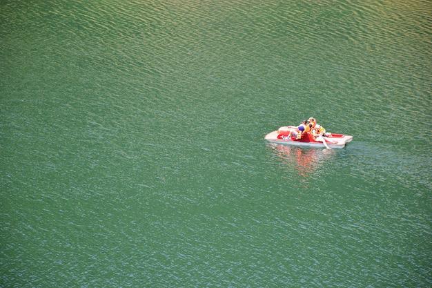 Una famiglia, genitori con due bambini, sta navigando su un fiume o un lago su un catamarano. fotografato da lontano, con un'angolazione elevata, c'è spazio a sinistra per inserire testo