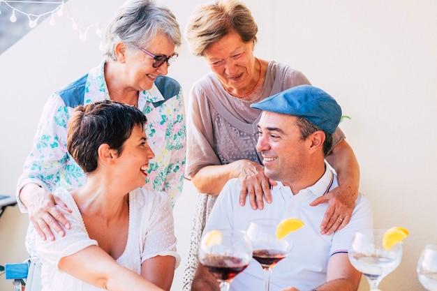 Ritratto allegro di persone di famiglia con madri e figlio che si abbracciano e si godono l'amicizia