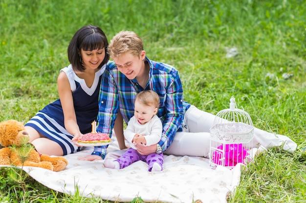 Famiglia che fa picnic all'aperto con la loro figlia carina.