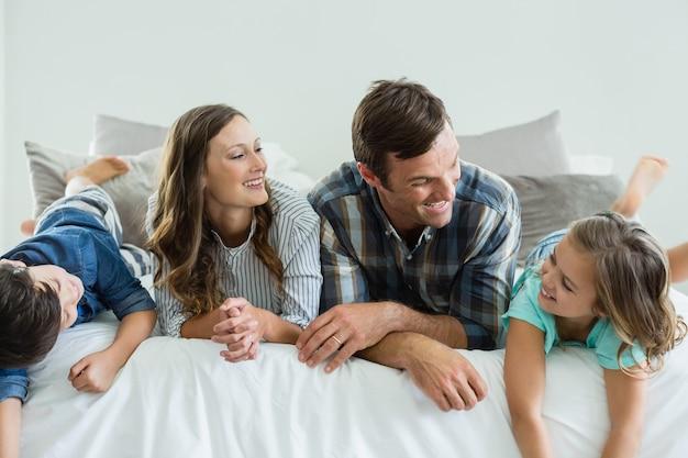 Famiglia che gioca sul letto in camera da letto a casa