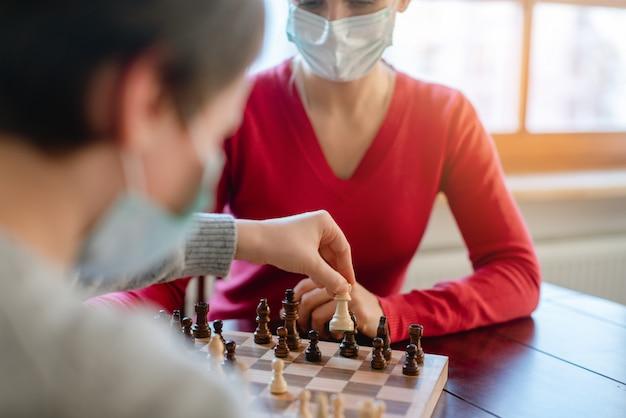 Famiglia giocando a giochi da tavolo durante il coprifuoco in movimento pezzi degli scacchi